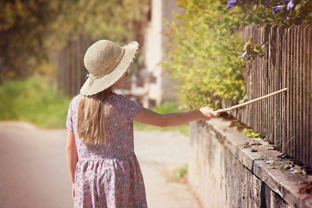 Niña rubia con sombrero de paja y vestido de flores pasea por pueblo y golpea una verja con un palo de madera