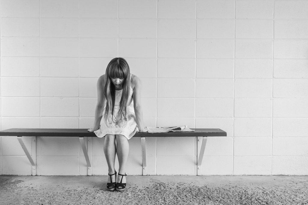 Chica sentada en banco de vestuario, mirando al suelo