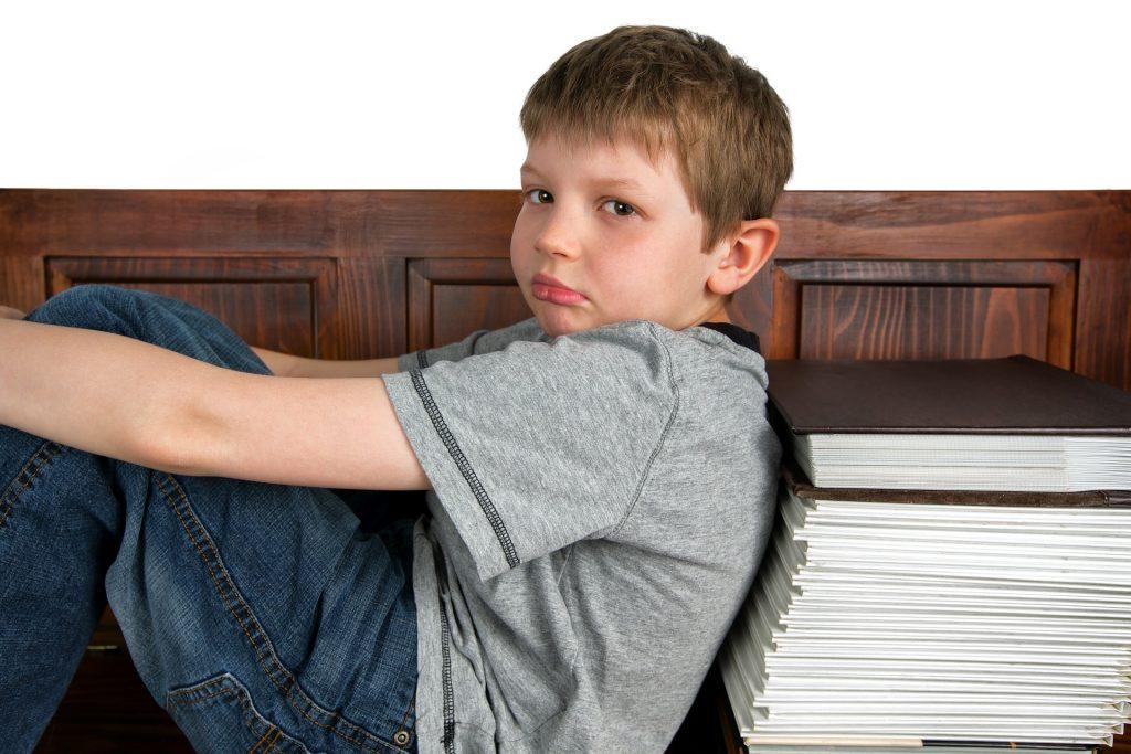 Niño con gesto aburrido apoyado en una pila de libros