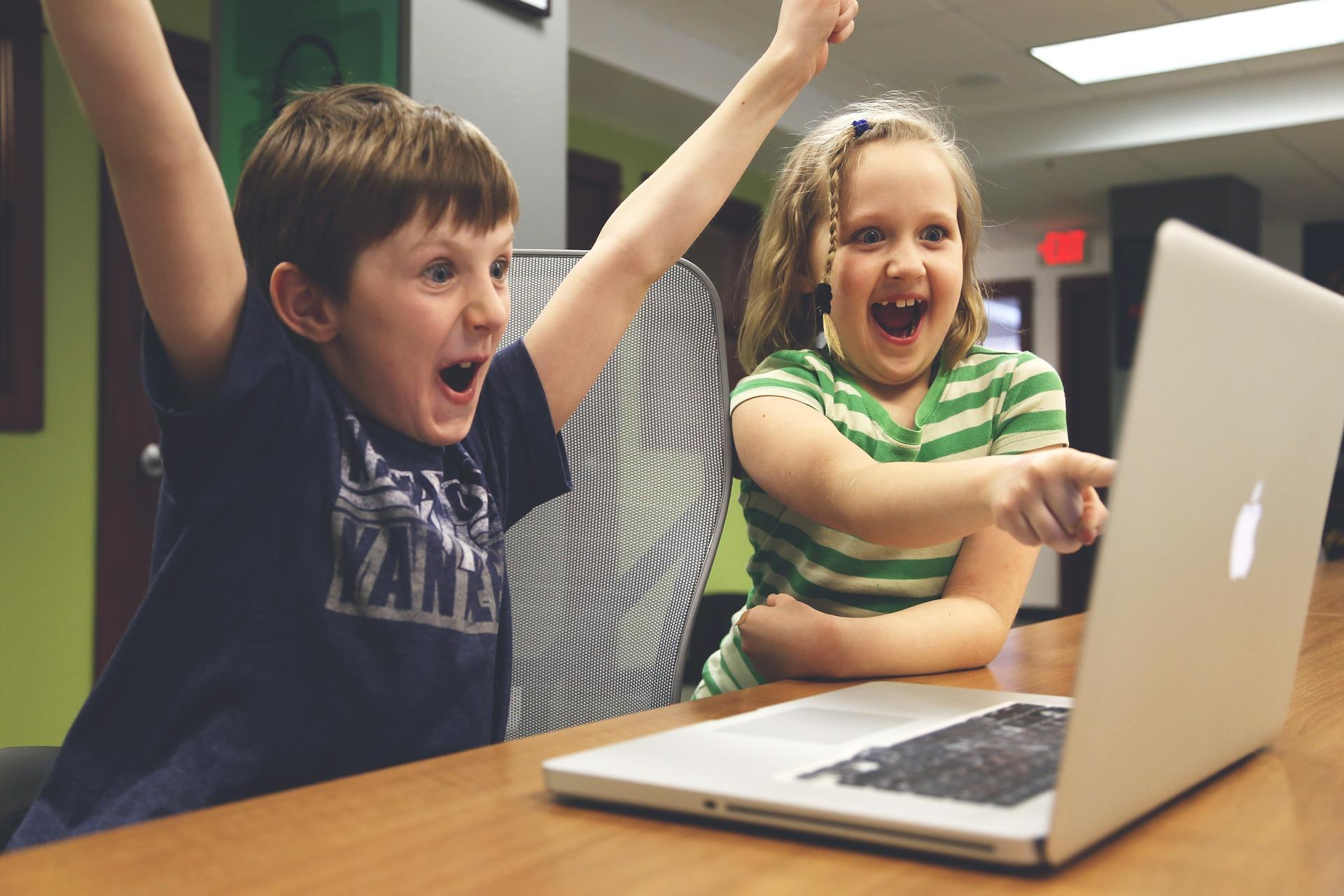 Dos niños miran la pantalla de un ordenador con expresiones de victoria y sorpresa respectivamente