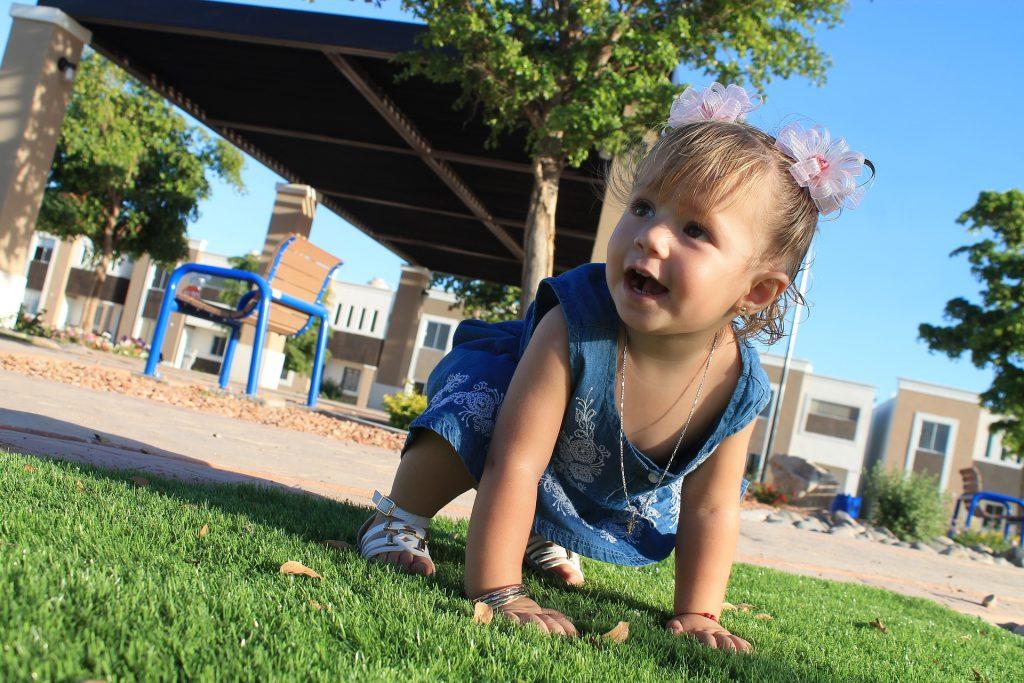 Niña pequeña gateando en el parque