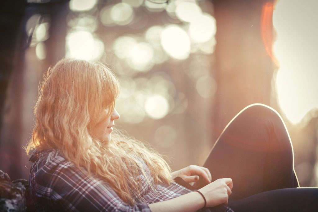 Chica rubia sentada en bosque