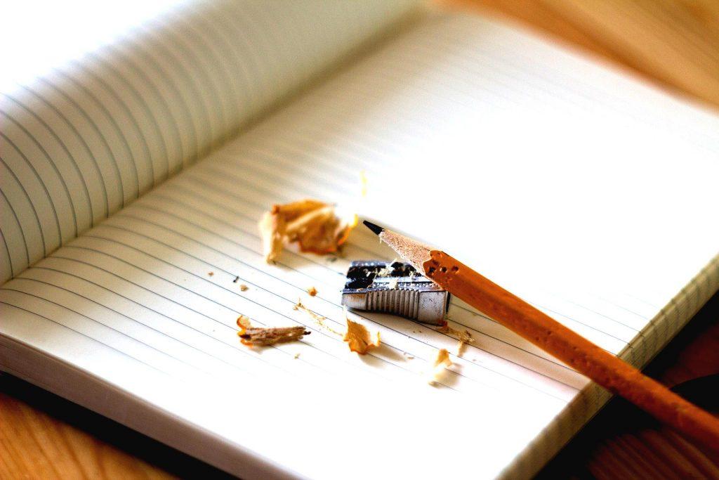 Lapicero recién afilado con punta y sacapuntas sobre cuaderno