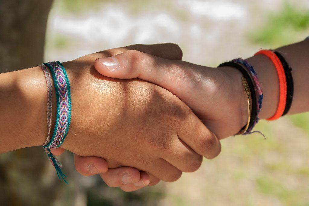dos niños se estrechan las manos