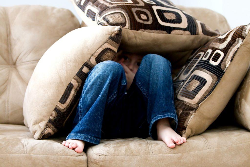 Niño escondido entre cojines, encima del sofá