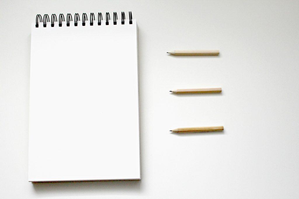 Cuaderno en blanco y tres lápices