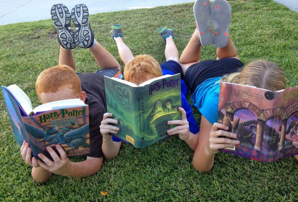 Tres niños leen Harry Potter tumbados en el césped