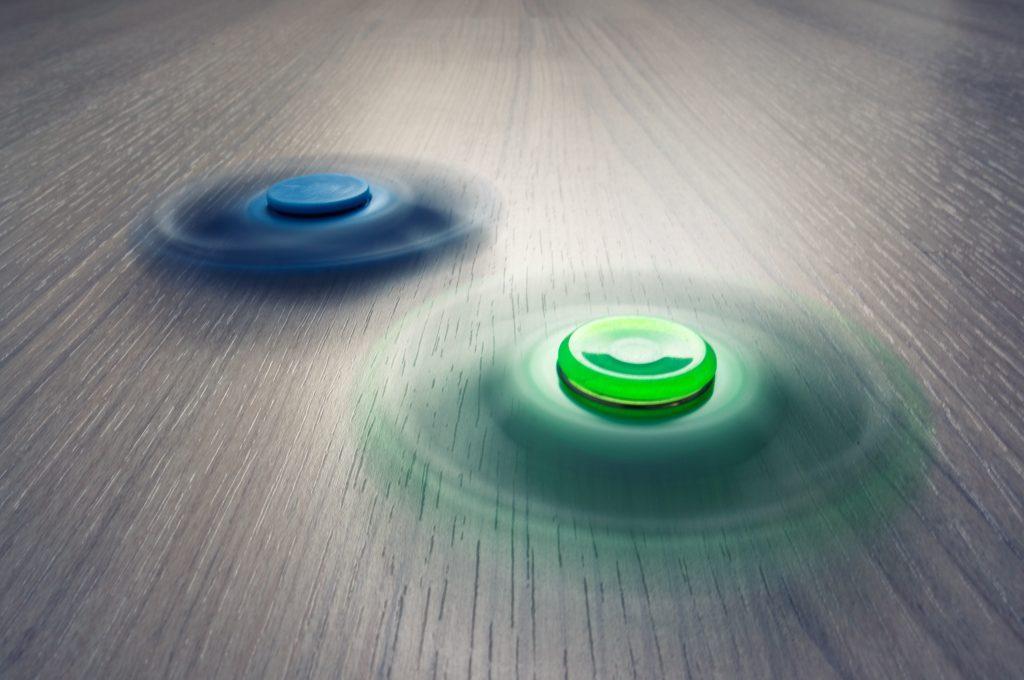 Dos peonzas, una verde y una azul, girando sobre superficie de madera