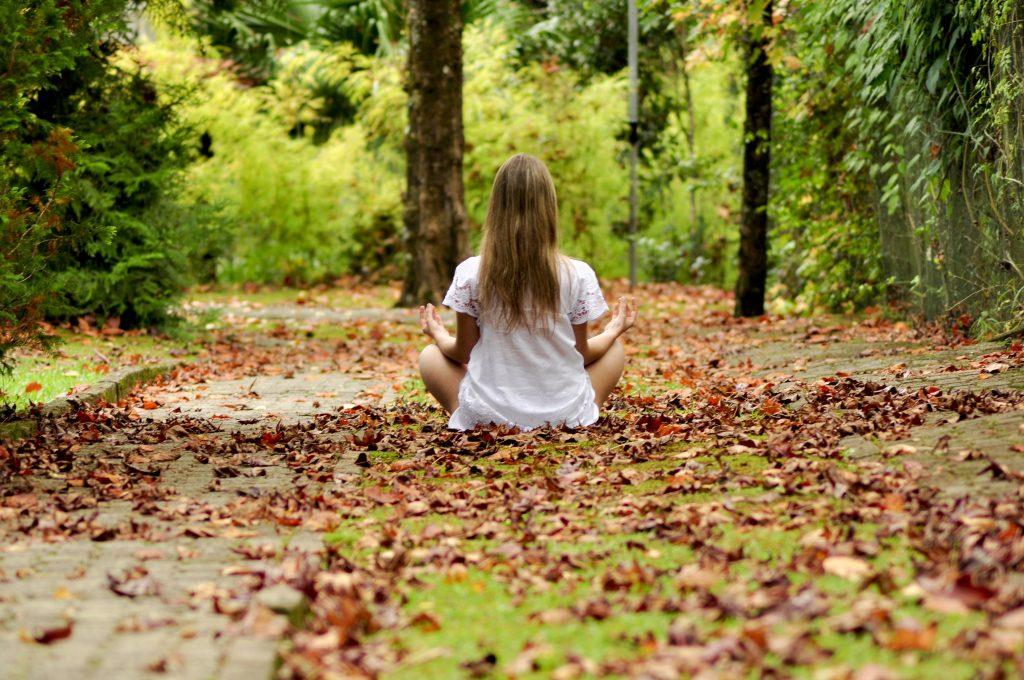 Niña meditando en bosque otoñal