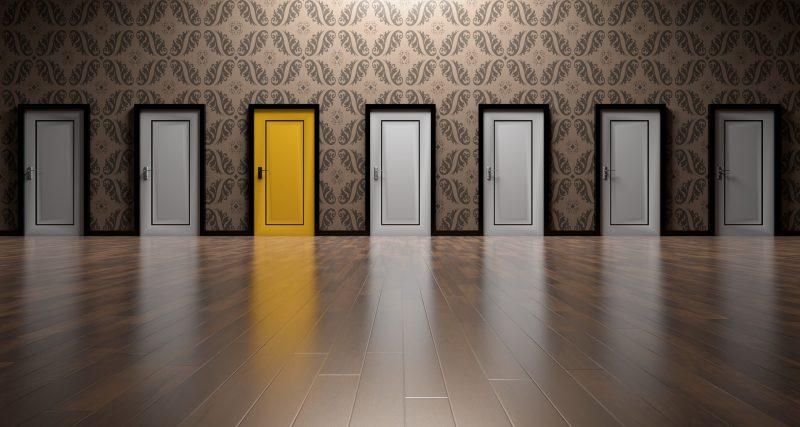 hilera de puertas en escenario interior. Seis están pintadas de color blanco, y una de ellas, la tercera, es amarilla.