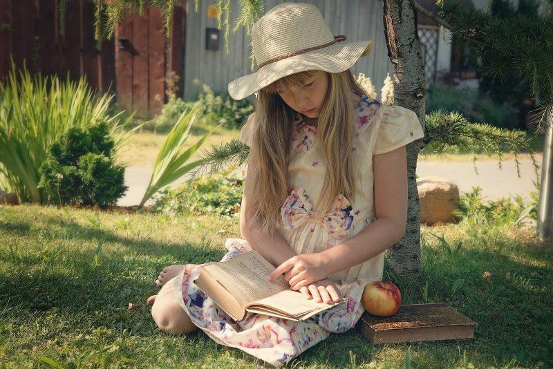 Niña rubia con vestido de estrellas y sombrero de paja, sentada junto a un árbol en el jardín, leyendo un libro. Junto a ella hay otro libro con una manzana encima.