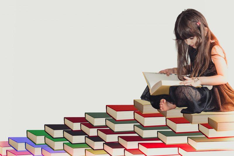 Niña leyendo, sentada sobre una montaña de libros