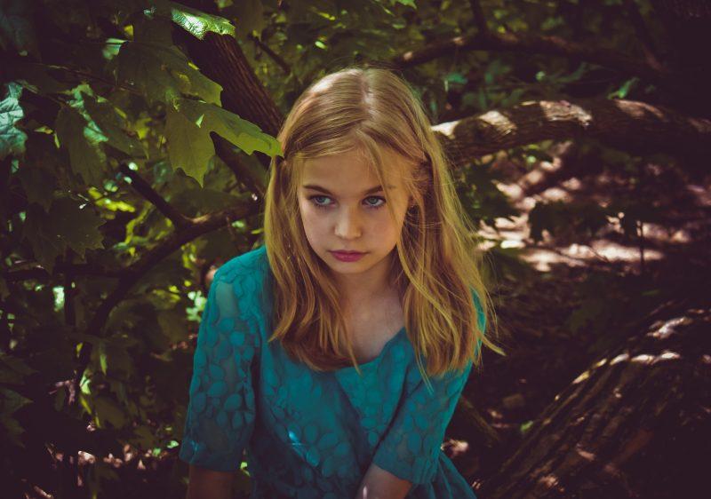 Niña rubia con vestido azul, encaramada en árbol
