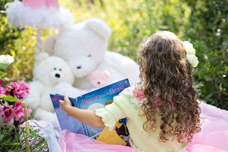 """Niña leyendo """"la Bella y la Bestia"""" en Inglés, sentada en el jardín junto a tres osos de peluche"""