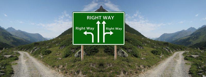 Camino de montaña que se divide a la cima; un cartel verde indica las ramificaciones.
