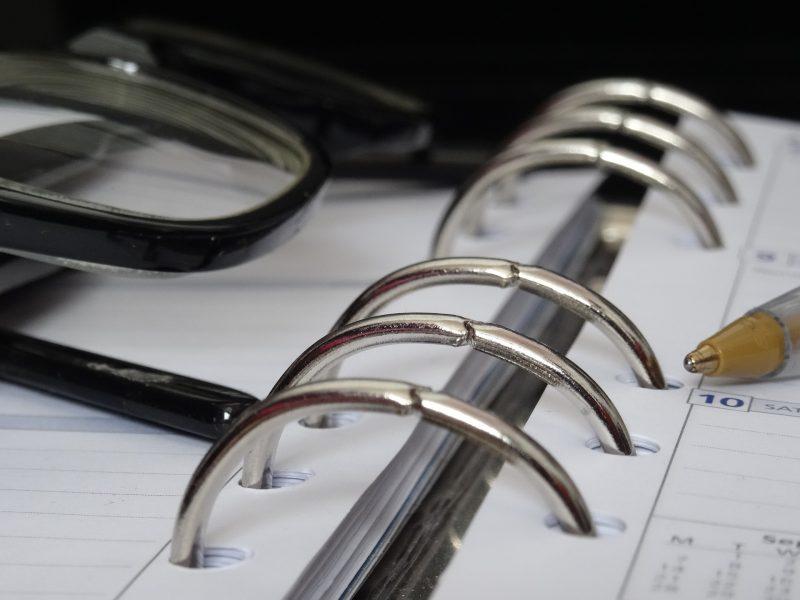 Agenda de anillas con bolígrafo y gafas sobre ella
