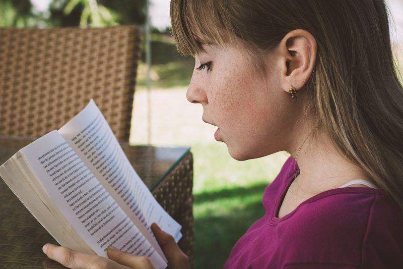 Niña leyendo en jardín
