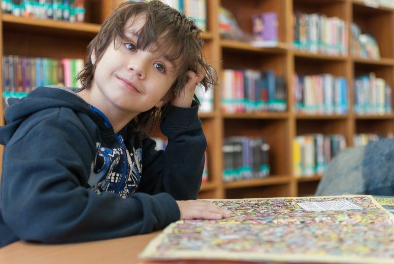 Niño sosteniendo un libro con dibujos en la mesa de una biblioteca.
