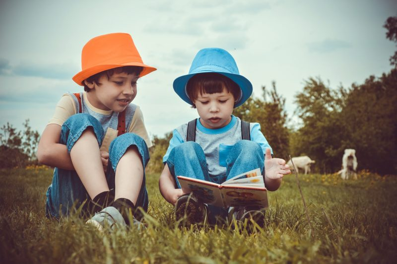 Dos niños con vaqueros y sombreros de colores vivos leen un libro sentados en el campo