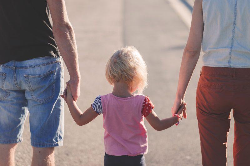 Niña camina cogida de las manos de sus padres