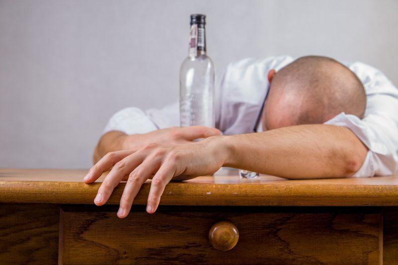 Persona recostada sobre una mesa sujetando una botella de alcohol