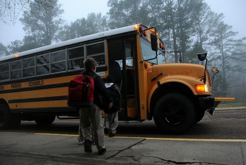Niños en la calle, haciendo cola para subir a un autobús escolar de color amarillo