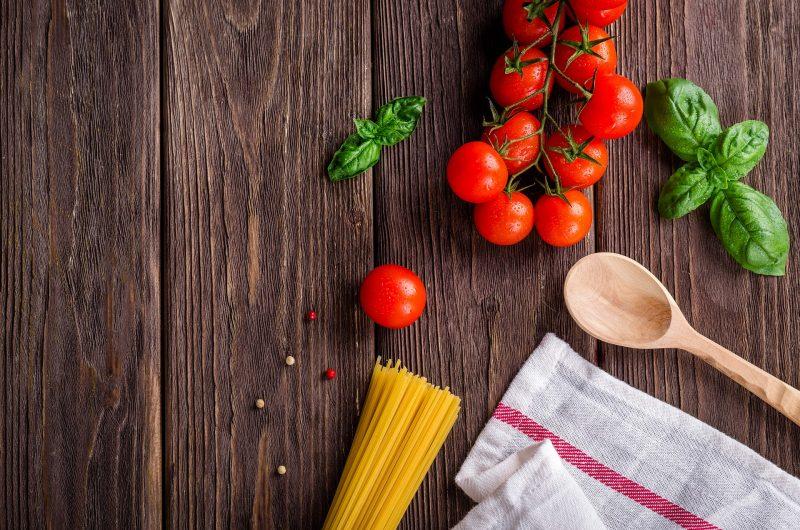 Tomates en rama, albahaca, pasta, granos de pimienta, cuchara y trapo sobre superficie de madera