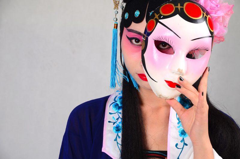 chica asiática, maquillada, sostiene junto a su cara una máscara pintada.