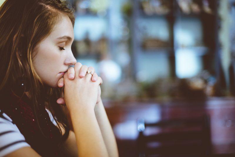 Joven en pose de rezar
