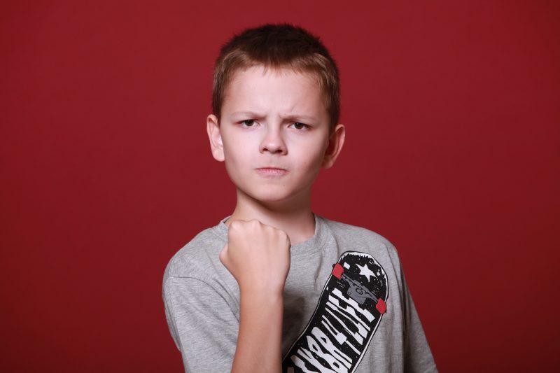 Niño con expresión de ira, levantando el puño cerrado