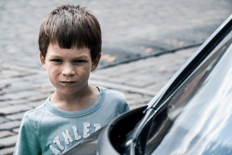 Niño con cara de enfado junto a vehículo