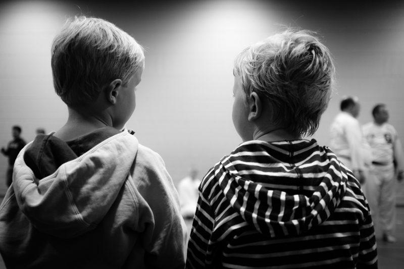 Dos niños, de espaldas a la cámara, interactúan entre ellos.