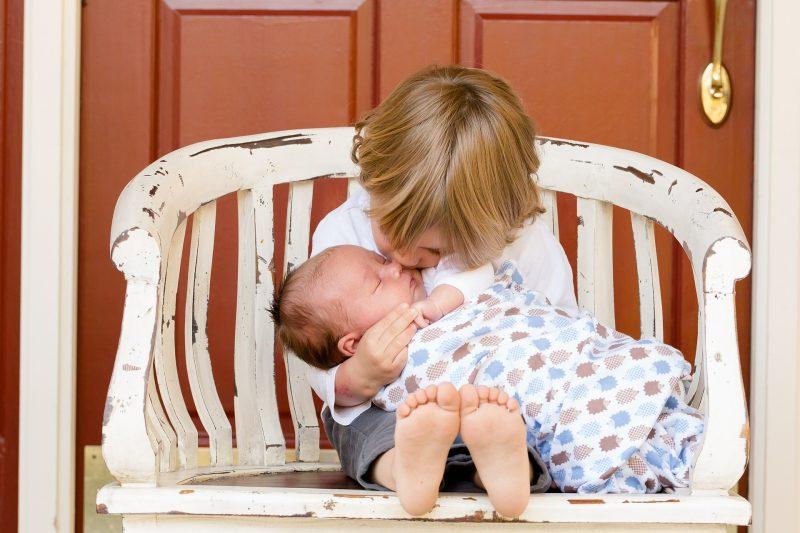 Niño pequeño sentado sobre una silla sujeta a un bebé y le besa la cabeza