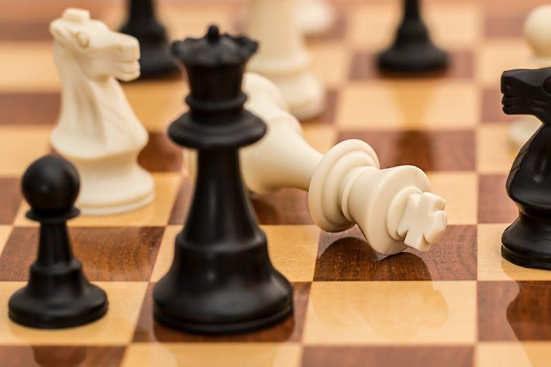 Piezas de Ajedrez en Tablero: negras juegan y ganan. Rey caído frente a reina.
