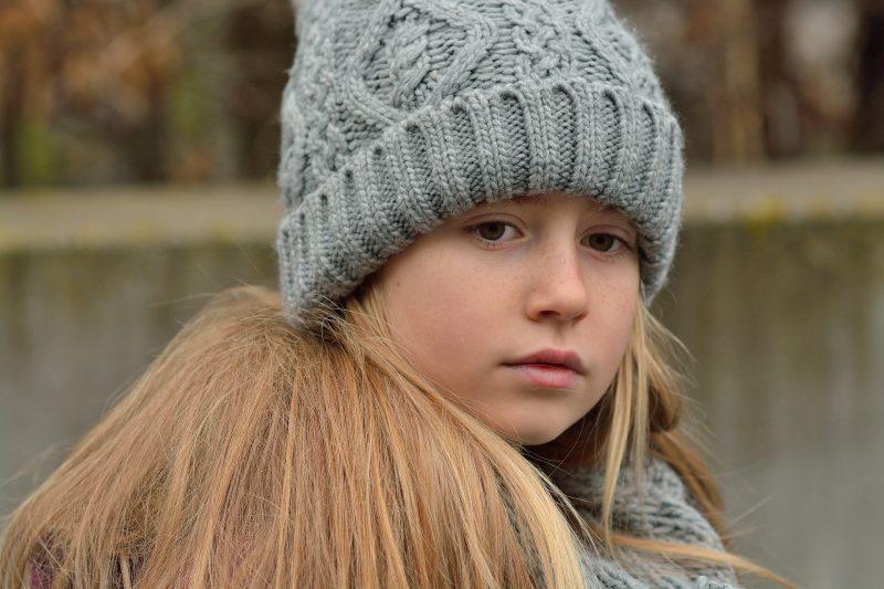 Niña rubia triste con gorro gris de lana