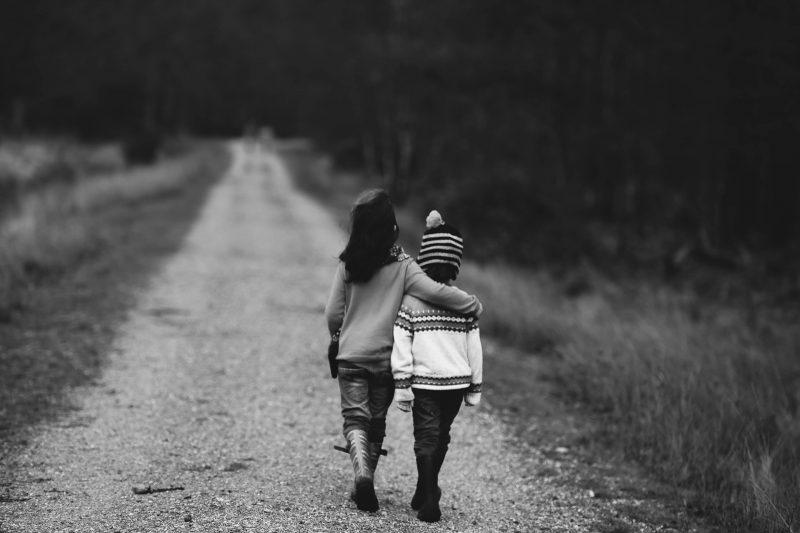 Dos niños caminan por un sendero con vegetación a ambos lados. La niña más alta le pasa el brazo por los hombros al más pequeño.