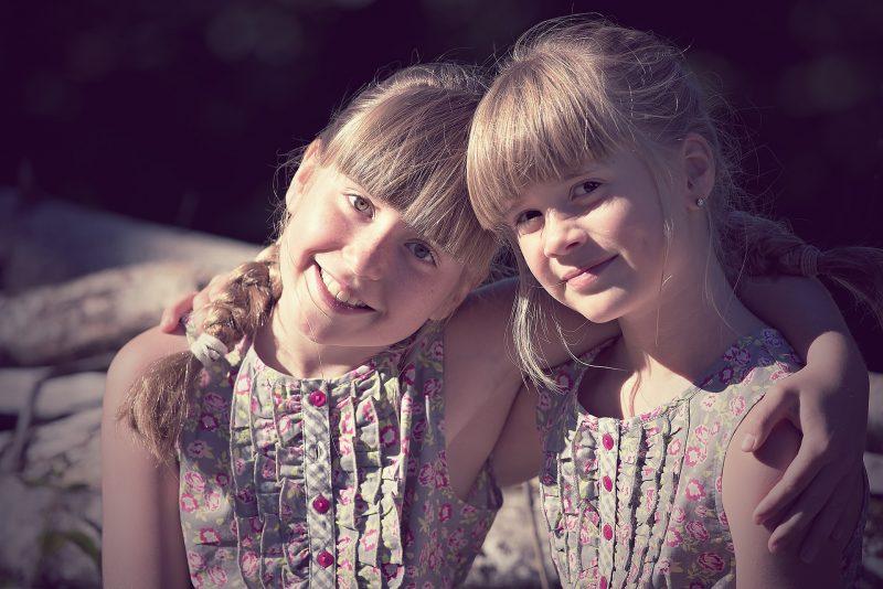 Dos niñas rubias con flequillo y vestidos verdes de flores, agarradas por los hombros