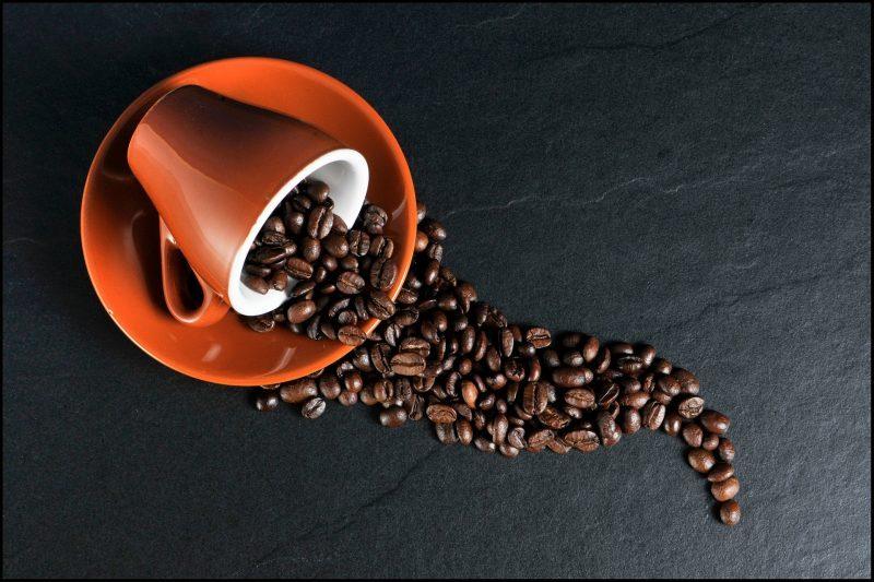 Taza volcada sobre plato, con granos de café cayendo desde la taza hasta el plato y la mesa.