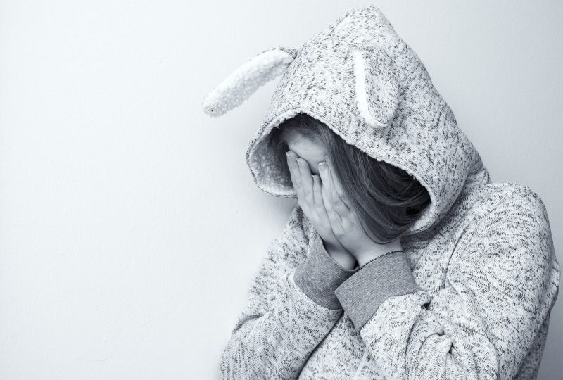 Niño con sudadera con orejas de conejo se tapa la cara con las manos