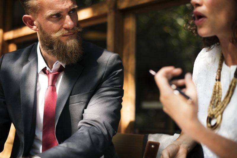 Hombre trajeado con barba y bigote escucha lo que le dice la mujer sentada a su lado
