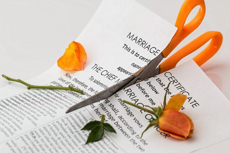 Certificado de matrimonio y flores siendo cortados