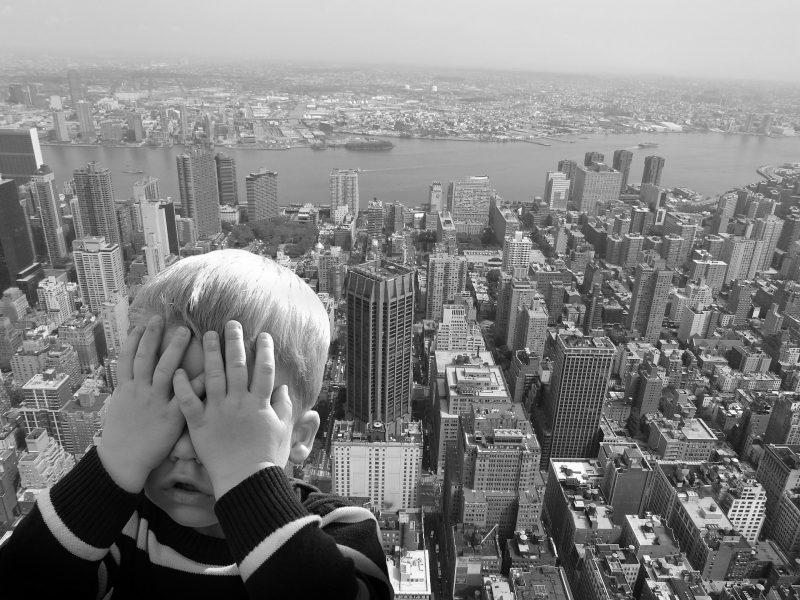Niño se tapa los ojos en un mirador frente a rascacielos