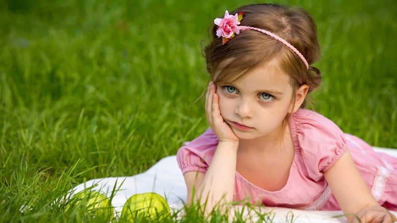 Niña tumbada en el césped, con vestido y diadema rosas, apoya su cara sobre su mano con expresión de contrariedad.