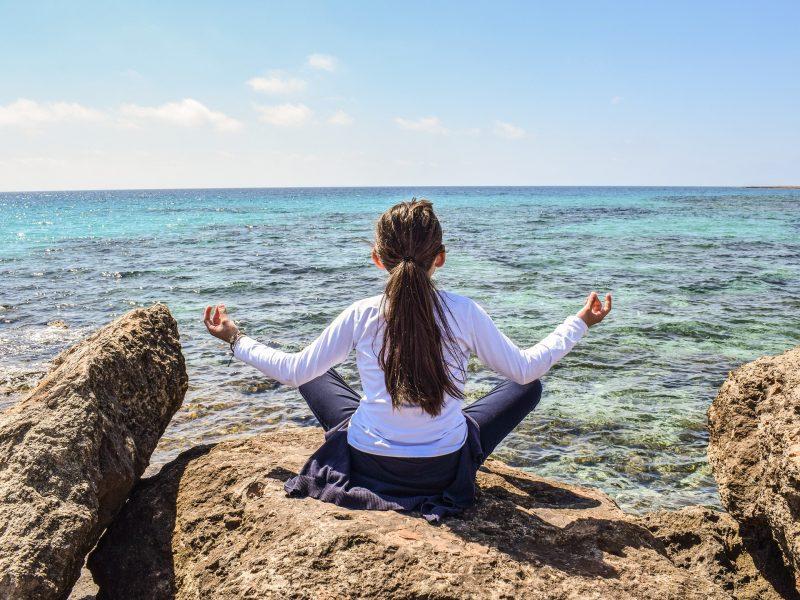 Niña haciendo yoga frente al mar