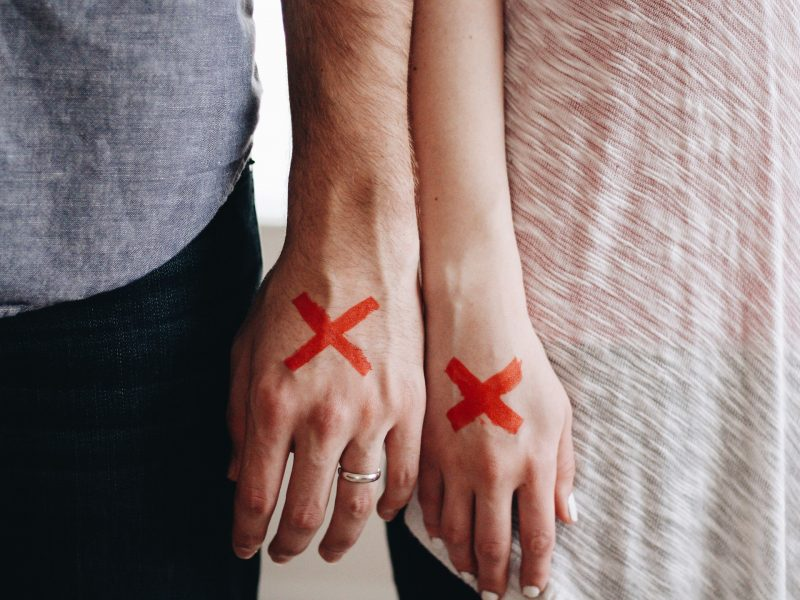 Manos de hombre y mujer con una X roja pintada sobre el dorso