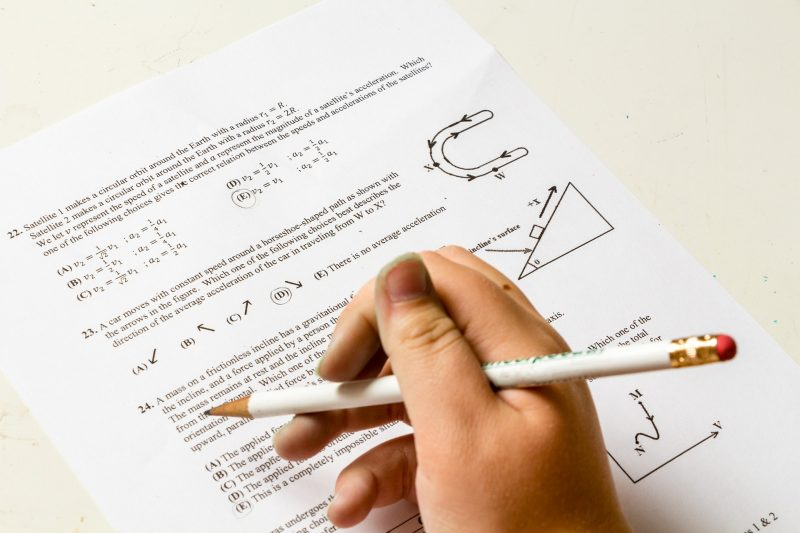 Mano infantil agarrando lapicero blanco, sobre un examen de matemáticas en inglés
