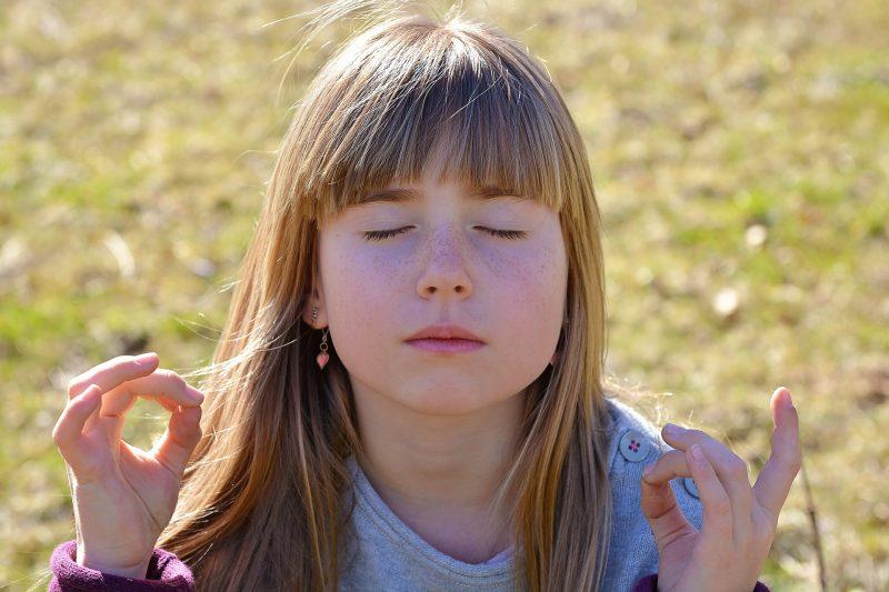 Niña meditando en el campo