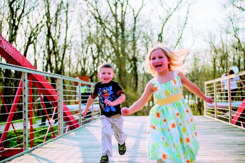 Dos niños corriendo por un puente