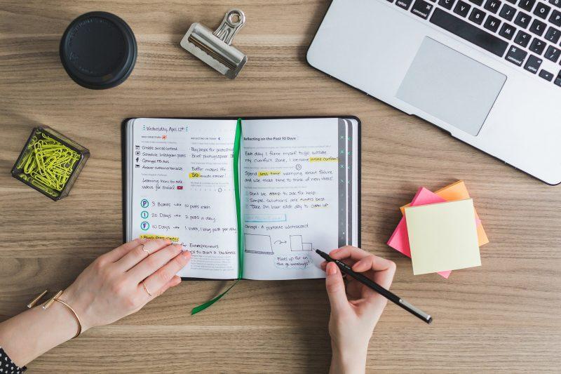 Persona escribiendo en cuaderno sobre una mesa, con post-its, clips, bote negro y portátil junto a ella. Imagen vista desde arriba.