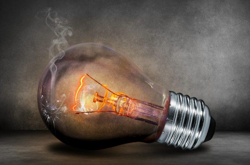 bombilla encendida apoyada sobre el suelo en posición horizontal, con el cristal roto y humo saliendo de la abertura
